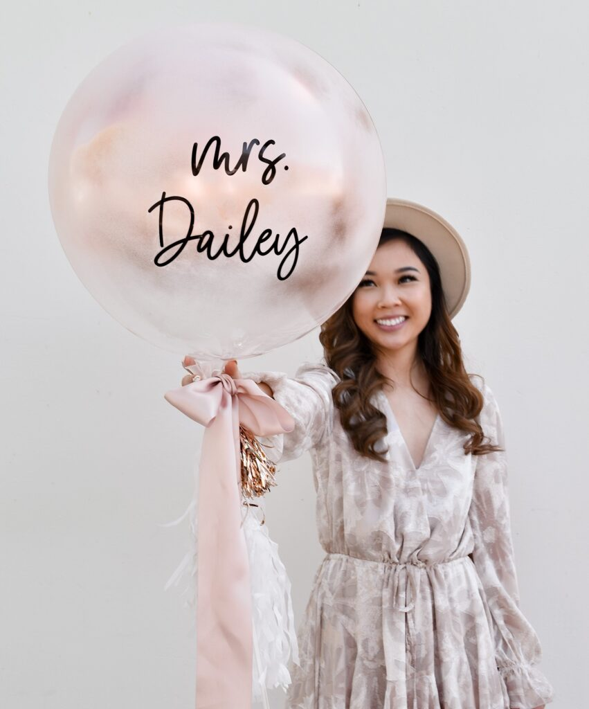 Girl holding finished DIY spray paint engagement balloon